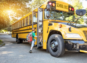 Child enters school bus at bus stop.