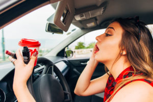Young woman distracted driving in car