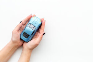 Car insurance concept, hands holding toy car