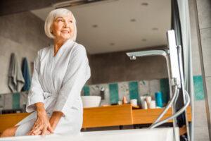 Older woman getting ready in bathroom using talcum powder